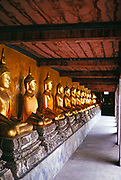 Line of sitting golden Buddha statues, Wat Pho temple, Bangkok, Thailand, Asia in 1964