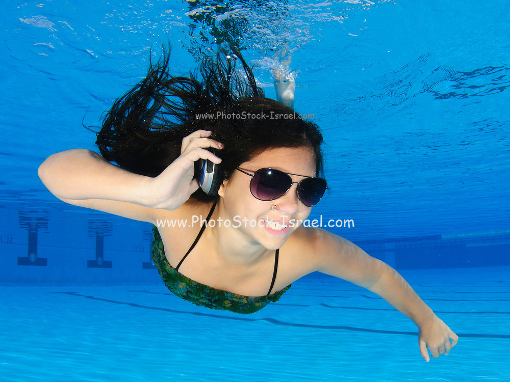 A dressed 12 year old female teen free diving underwater in a swimming pool with headphones and sunglasses. Model release available