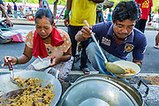 "11 MAY 2013 - BANGKOK, THAILAND: Protesters line up for breakfast. Several hundred small scale family farmers camped out ""Government House"" (the office of the Prime Minister) in Bangkok to Thai Prime Minister Yingluck Shinawatra to deliver on her promises to improve the situation of family farmers. The People's Movement for a Just Society (P-move) is a network organization which aims strengthen the voices of different, but related causes working to bring justice for marginalized groups in Thailand, including land rights for small-scale farmers, citizenship for stateless persons, fair compensation for communities forced to relocate to accommodate large scale state projects, and housing solutions for urban slum dwellers, among others.   PHOTO BY JACK KURTZ"