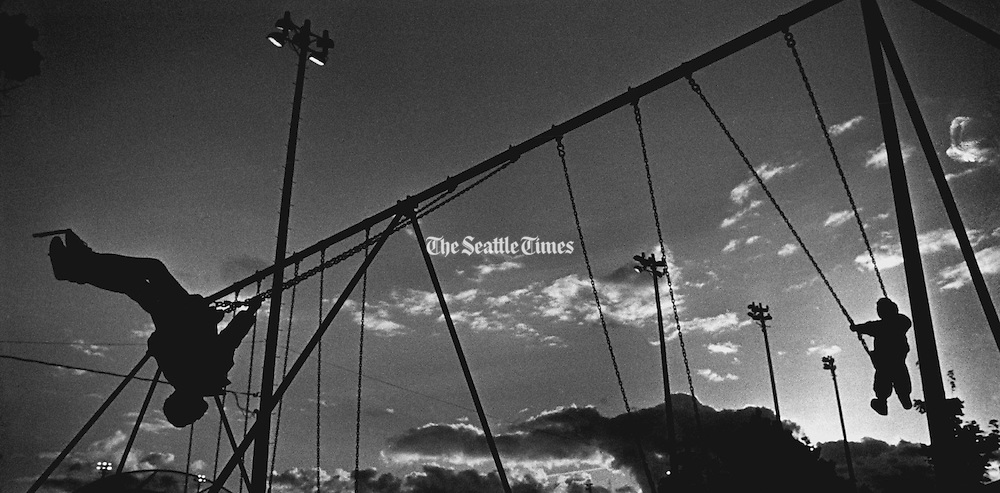 Brothers swing at Garfield Playfield as the rain lets up. (Jim Bates / The Seattle Times, 1990)