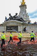 """Police rushing to apprehend and arrest Animal and climate activists, Animal Rebellion, after they dyed blood-red Buckingham Palace fountains on Thursday, Aug 26, 2021 - signifying as their statement said """"its' demonstrable role in hunting and animal agriculture"""". (VX Photo/ Vudi Xhymshiti)"""