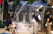 Investigators from the FBI and GBI (Georgia Bureau of Investigation) dust pay telephones for fingerprints left by the Olympic Park bomber after he called in a bomb threat to police dispatchers. Moments later the bomb exploded. Agents are also canvassing the bomb radius to collect evidence.