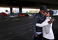 Raymond Joseph, 56, holds his fianceé Regina Carter, 40, at their encampment off of Martin Luther King Jr Way and 23rd St. in Oakland, Calif., on Friday, October 9, 2020. The couple are expecting a baby in seven months. The couple would like to have permanent housing before their baby arrives.  Oakland is in the midst of the worst homelessness crisis the city has ever seen. Overall homelessness in Oakland increased by 47% with a 68% increase from 2017 to 2019 in the number of unsheltered people from 1,902 to 3,210 people. There are an estimated 60 encampments of three or more people in Oakland with approximately 730 total people living in the encampments.