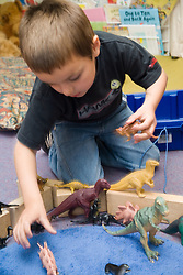 Boy kneeling on floor in classroom playing with toy dinosaurs,