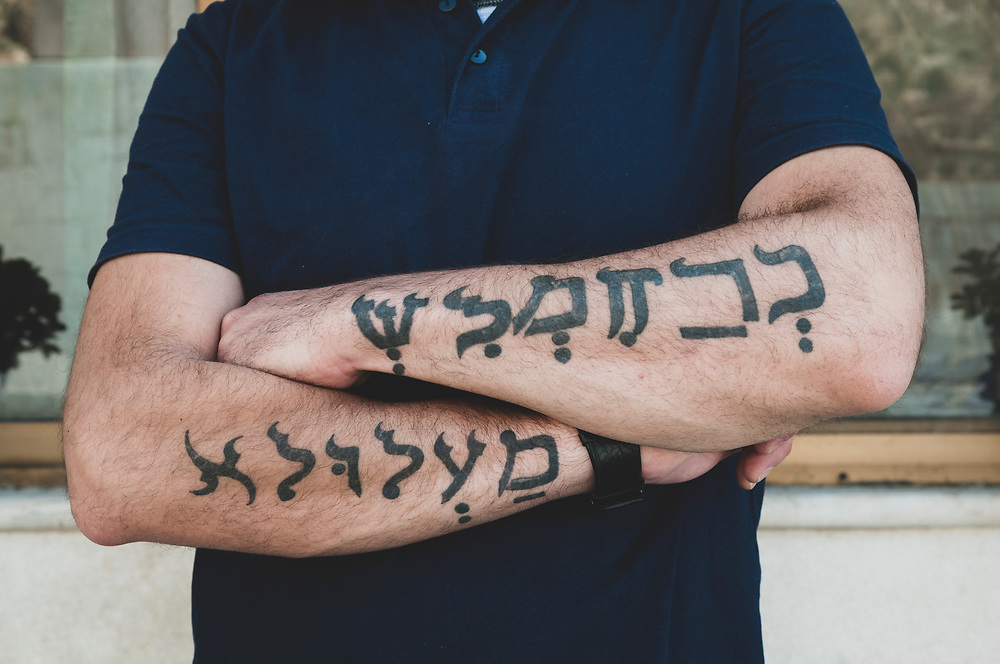 """A young Syrian Christian man stands outside his family's restaurant in the town of Maaloula, Syria. About half the population of Maaloula is Christian and speaks Aramaic as well as Arabic. The text of the tattoo, in Aramaic, reads """"I love Maaloula."""""""
