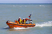3 volunteer crew members in a RNLI Inshore lifeboat - B-766 patrol the waters around Folkestone Harbour, Folkestone, Kent. UK. 6th August 2016.