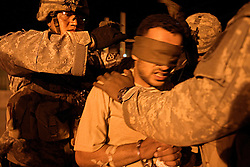 Members of the 1st Infantry, 17th Regiment, transport captured insurgent Imad Shaeb, also known as Adel, to the Iraqi Army Battalion 222, Mosul, Iraq, Dec. 11, 2005. American troops are helping Iraqi forces in preparation for Iraq's first post-Saddam parliamentary elections. The western sector is home to Mosul's primarily Sunni population, which has been resistant to the American presence in Iraq.