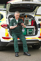 Pictured: Ian Stark checks the new tablet fitted to vehicles in Scottsih Ambulance Service<br /> <br /> Health Secretary Shona Robison met paramedics today on a visit to Scottish Ambulance Service's city station where she announced new funding for the service<br /> Ger Harley   EEm 24 April 2017