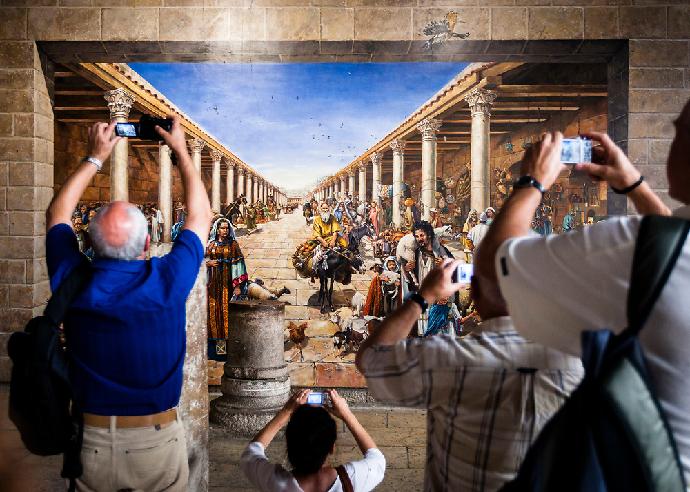 Tourists and visitors photograph of a mural showing an ancient market, at the Cardo, a north-south oriented main street constructed in the Roman period, in the Jewish Quarter of the Old City of Jerusalem