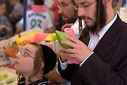 Israel, Bnei Brak, Closely examining an Etrog at the Sukkoth 4 species market.