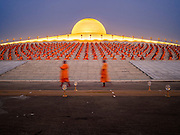 """22 FEBRUARY 2016 - KHLONG LUANG, PATHUM THANI, THAILAND: Monks and novices file into the chedi before the evening service for Makha Bucha Day at Wat Phra Dhammakaya.  Makha Bucha Day is a public holiday in Cambodia, Laos, Myanmar and Thailand. Many people go to the temple to perform merit-making activities on Makha Bucha Day, which marks four important events in Buddhism: 1,250 disciples came to see the Buddha without being summoned, all of them were Arhantas, Enlightened Ones, and all were ordained by the Buddha himself. The Buddha gave those Arhantas the principles of Buddhism, called """"The ovadhapatimokha"""". Those principles are:  1) To cease from all evil, 2) To do what is good, 3) To cleanse one's mind. The Buddha delivered an important sermon on that day which laid down the principles of the Buddhist teachings. In Thailand, this teaching has been dubbed the """"Heart of Buddhism."""" Wat Phra Dhammakaya is the center of the Dhammakaya Movement, a Buddhist sect founded in the 1970s and led by Phra Dhammachayo. The temple is famous for the design of its chedi, which some have likened to a flying saucer or UFO.            PHOTO BY JACK KURTZ"""