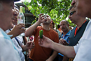 Moscow, Russia, 25/07/2010..Men drink vodka as hundreds of Russians gather at the grave of legendary bard singer, poet and actor Vladimir Vysotsky to mark the 30th anniversary of his death. Vysotsky, an alcoholic and heroin addict who died in 1980 aged 42 of a heart attack, is best known for his songs of Soviet prison and military life, and his acting on stage and screen. Much of his work was officially unpublished during his lifetime, and he remains a potent anti-authoritarian symbol of protest to Russians of all ages even today.