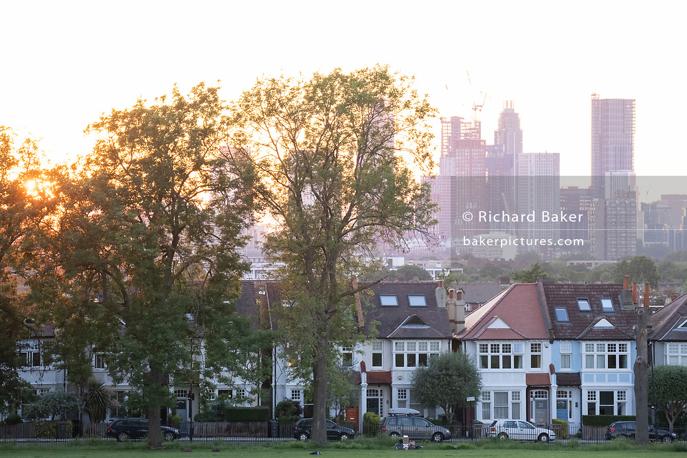 With the tall towers at Nine Elms in the distance, a sun sets below a line of homes and ash trees in Ruskin Park, a public green space in Lambeth, south London, on 12th June 2021, in London, Englnd.
