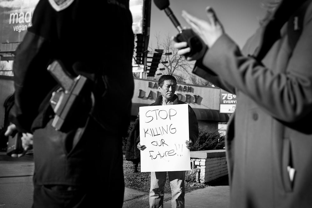 Tigme Nortn, center, holds a protest sign as Madison Police Chief Mike Koval is interviewed by the media during a protest in Madison, Wisconsin, March 11, 2015. Protestors rallied for the fifth day in a row, after the shooting death of Tony Robinson, Jr. by Madison Police inside his home on March 6, 2015. REUTERS/Ben Brewer (UNITED STATES)