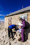 Hikers signing the summit register on Mount Whitney, Sequoia National Park, Sierra Nevada Mountains, California USA