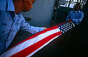 Two US Navy sailors carefully fold the nation's on an upper deck of the aircraft carrier USS Harry S Truman. The Truman is the largest and newest of the US Navy's fleet of new generation carriers, a 97,000 ton floating city with a crew of 5,137, 650 are women. The Iraqi no-fly zones (NFZs) were proclaimed by the United States, United Kingdom and France after the Gulf War of 1991 to protect humanitarian operations in northern Iraq and Shiite Muslims in the .