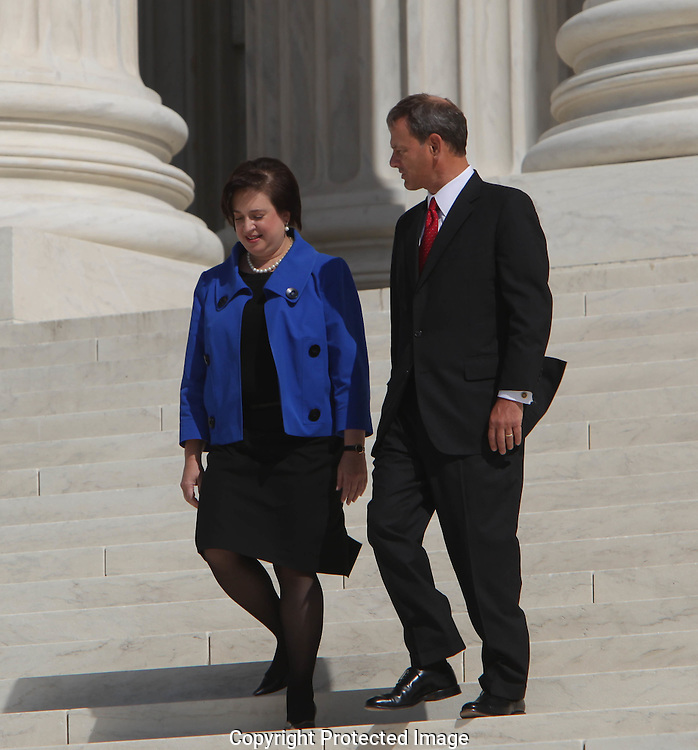 Supreme Court Chief Justice John Roberts and Supreme Court Associate justice Elena Kagan pose and walk down the steps of the Supreme Court after the investiture ceremony on October 1, 2010. Photograph by Dennis Brack