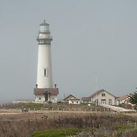 An historic lighthouse warns ships away from rocks near Pigeon Point on the Pacific Ocean coast near Pescadero, California.