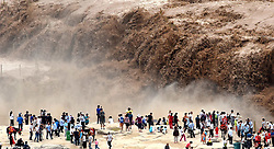 Aug. 24, 2017 - Linfen, China -  People visit the Hukou Waterfall on the Yellow River on the border area between Jixian County of north China's Shanxi and Yichuan County of northwest China's Shaanxi provinces. Due to heavy rainfall at the upper reaches, the water volume of Hukou Waterfall surged. (Credit Image: © Lyu Guiming/Xinhua via ZUMA Wire)