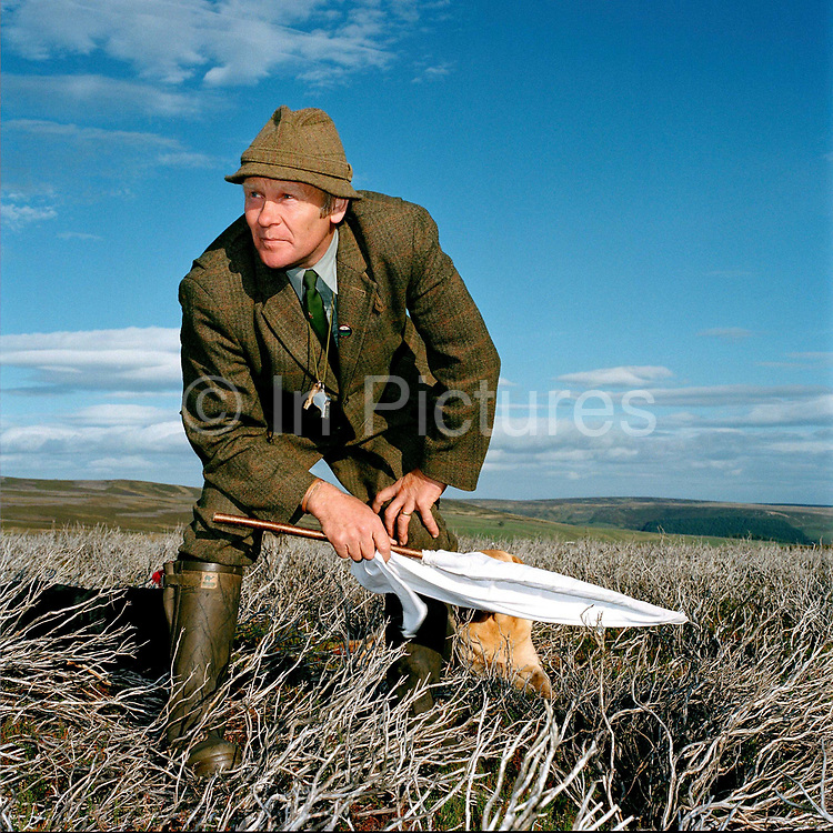 A flanker standing on the Moor and waiting during a grouse shoot in Upper Nidderdale, North Yorkshire, UK. The flankers job is to drive the grouse using a flag back towards the 'guns' who are waiting in the shooting butts.
