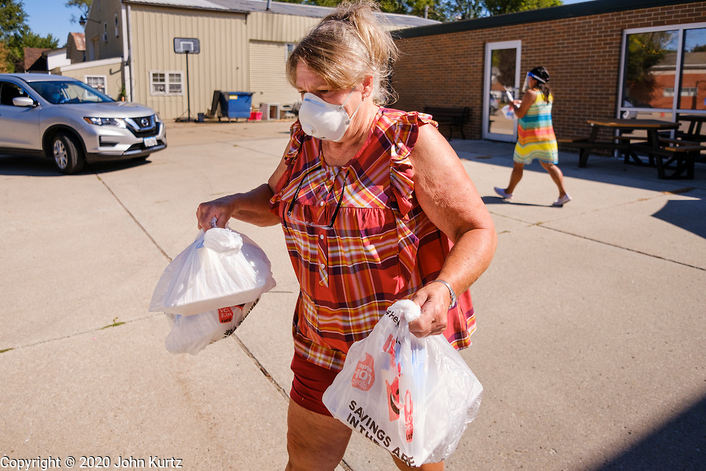 """02 SEPTEMBER 2020 - MITCHELLVILLE, IOWA: JOAN ALLSUT takes hot meals to her car to deliver them to people in Mitchellville. There is no grocery store in Mitchellville, a small community in eastern Polk County. It doesn't qualify as a """"food desert"""" under USDA guidelines because there are grocery stores within 10 miles in neighboring communities, but based on state data, Mitchellville is the poorest community in Polk County (which includes the Des Moines metropolitan area). The Mitchellville zip code has the lowest per capita income in Polk County. Many people don't own cars and can't get to neighboring communities to buy groceries. The library in Mitchellville has made arrangements with a neighboring community. Every day someone from the Mitchellville library picks up hot meals from a nearby town and distributes them in the library parking lot.      PHOTO BY JACK KURTZ"""