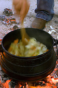 Cooking on an open fire, a small caldron on an outdoor wood fire, hand stirring the broth