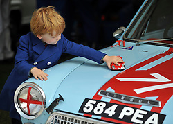© Licensed to London News Pictures. 17/09/2011. GOODWOOD, UK. Arthur Allenby - Byrne plays with a reproduction Alpha Daytona on the bonnet of his fathers 1964 Ford Cortina GT. Arthur celebrated his sixth Birthday on Day one of Goodwood this year. He was born six years ago when his father was racing the same car at Goodwood. The Goodwood Revival at Goodwood in West Sussex today (17 September 2011). The revival is the world's largest historic motor race meeting, which relieves the 'glorious' days of the race circuit. Competitors and enthusiasts all dress in period fashion to enhance the experience. Photo credit : Stephen Simpson/LNP