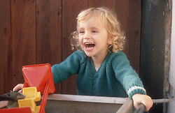 Young girl playing in playground laughing,