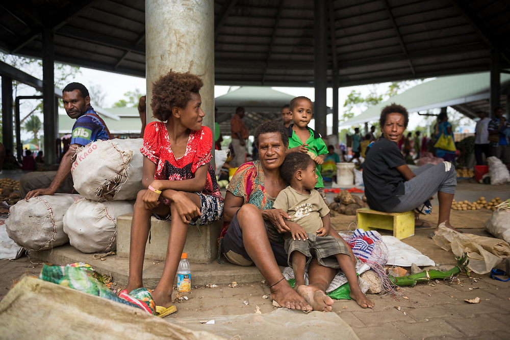 Adults and children sit at the open-air market in Madang, Papua New Guinea.