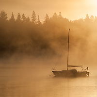 A silhouette of a sailboat at sunrise on the Connecticut Lakes, Pittsburg, New Hampshire.<br /> <br /> All Content is Copyright of Kathie Fife Photography. Downloading, copying and using images without permission is a violation of Copyright.