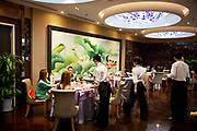 Waiting staff and customers in the main dining room. Quanjude roast duck restaurant in Wangfujing, Beijing. This is a Chinese restaurant known for its trademark Peking Roast Duck and is known for being the best roast duck restaurant in China. Quanjude was established in 1864 during the Qing Dynasty under the reign of the Tongzhi Emperor. Although Peking Duck can trace its history many centuries back, Quanjude's heritage of roast duck preparation - using open ovens and non-smoky hardwood fuel such as Chinese date, peach, or pear to add a subtle fruity flavor with a golden crisp to the skin, was originally reserved for the imperial families.