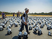 "04 MARCH 2016 - BANGKOK, THAILAND: A panda wrangler carries a couple of paper maché pandas for the ""1600 Pandas+ World Tour in Thailand: For the World We Live In and the Ones We Love"" opening on Sanam Luang in Bangkok. The 1600 paper maché pandas, an art installation by French artist Paulo Grangeon will travel across Bangkok and parts of central Thailand for the next week and then will be displayed at Central Embassy, a Bangkok shopping mall, until April 10. The display of pandas in Thailand is benefitting World Wide Fund for Nature - Thailand and is sponsored by Central Embassy with assistance from the Tourism Authority of Thailand and Bangkok Metropolitan Administration and curated by AllRightsReserved Ltd.     PHOTO BY JACK KURTZ"