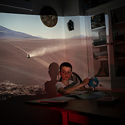 Oliver doing his school homework with slide of Atacama Desert projected onto the kitchen wall.