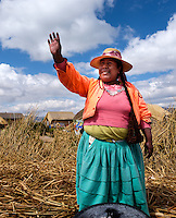 UROS ISLANDS, PERU - CIRCA October 2015: Woman from the Uros waving hands and welcoming people in the floating Islands of Lake Titicaca.