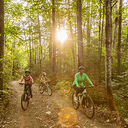A woman and her kids ride bikes near Deboullie Pond in Aroostook County, Maine. Deboullie Public Reserve Land.