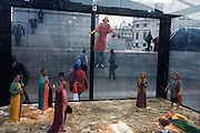 A holy nativity scene titled Christmas Crib by the artist Tomoaki Suzuki with background tourists in London's Trafalgar Square