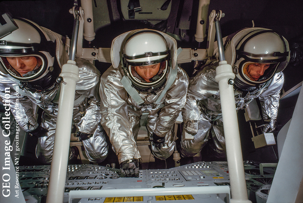Research engineers enact a lift-off in a space capsule mockup.