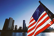 Chicago skyline at sunset.  Seen from Lake Michigan with American flag in foreground, Illinois, USA.