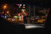 Man and woman walk at night through the streets in Tijuana, Mexico. SPANISH: Una pareja camina en la noche por las calles de Tijuana, México.