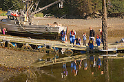 USA, ALASKA, Family searching tide pool for sea creatures, fishing boat in back ground, Tutka Bay Lodge near Homer.