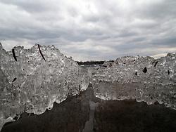 Still water lies beneath a heaving ice sheet on Lake Nokomis during spring thaw