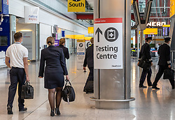 "© Licensed to London News Pictures. 09/04/2021. London, UK. Flight attendants walk past a test centre sign at London Heathrow. Today, Transport Secretary Grant Shapps sets out details of the government's ""traffic Light"" system for May 17th so that the public can travel abroad with passengers requiring to take a private covid-19 test each way, costing as much as £150.00 for one test. Photo credit: Alex Lentati/LNP"