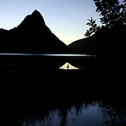 A photographer takes pictures of Mitre Peak at sunset. Mitre Peak is an iconic mountain in the South Island of New Zealand. It is one of the most photographed peaks in the country. Part of the reason for its iconic status is its location. Close to the shore of Milford Sound, in the Fiordland National Park in the southwestern South Island, it is a stunning sight. Rising to 1,692 metres from the water of the sound. it is actually a closely grouped set of five peaks, although from most easily accessible viewpoints it appears as a single point. Milford Sound,  Milford Sound, New Zealand. 29th April 2011. Photo Tim Clayton