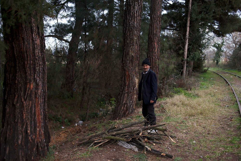 A Kurdish-Syrian man gathers wood for fire near the border between Greece and Macedonia in Idomeni, Greece. Around 13,000 migrants and refugees, mostly from the Middle East and African nations, are believe to be stranded here awaiting a chance to proceed their journey towards Germany and other northern European countries.