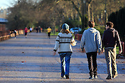 Teenagers walking along the Thames Path, at Battersea Park, SW London