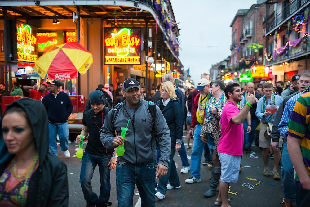 Mardi Gras revelers walk down Bourbon Street in the French Quarter at dusk in New Orleans.