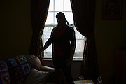 An unidentified lady stands silhouetted in front of her living room window.  London, UK.
