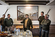 """Luis Orvalho giving a speech with safety rules before the hunt. <br /> <br /> """"The Pose and the Prey""""<br /> <br /> Hunting in my imagination was always more like taxidermy — as if the prey was just a mere accessory of the hunter's pose for his heroic photograph — the real trophy.<br /> <br /> When I decided to document the daily lives of Portuguese hunters, I had in my memory the """"cliché"""" from the photographer José Augusto da Cunha Moraes, captured during a hippopotamus hunt in the River Zaire, Angola, and published in 1882 in the album Africa Occidental. The white hunter posed at the center of the photograph, with his rifle, surrounded by the local tribe.<br /> <br /> It was with this cliché in mind that I went to Alentejo, south of Portugal, in search of the contemporary hunters. For several months I saw deer, wild boar, foxes. I photographed popular hunting and private hunting estates, wealthy and middle class hunters, meat hunters and trophy hunters. I photographed those who live from hunting and those who see it as a hobby for a few weekends during the year. I followed the different times and moments of a hunt, in between the prey and the pose, wine and blood, the crack of gunfire and the murmur of the fields .<br /> <br /> I was lucky, I heard lots of hunting stories. I found an essentially old male population, where young people are a minority. Hunters, a threatened species by aging and loss of economic power caused by the crisis in the South of Europe.<br /> <br /> The result of this project is this series of contemporary images, distant from the """"cliche"""" of 1882.<br /> <br /> — Antonio Pedrosa"""