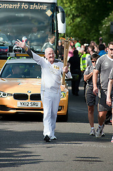 The Olympic Torch relay reaches Sheffield on day 38 coverage from the Chapeltown - Ecclesfield - Parson Cross section of the Journey.<br /> Torch bearer 105 73 year old John Burkhill takes the flame on up towards Ecclesfield Schools main gate<br /> 25 June 2012.Image © Paul David Drabble