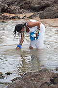 Middle aged Brazilian woman, in traditional Candomble dress of white, washing herself in prayer and making offerings of flowers to the sea in honour of Yemanja. February 2nd is the feast of Yemanja, a Candomble Umbanda religious celebration, where thousands of adherants visit the Rio Vermehlo Red River to pay their respects to Yemanja, the Orixa goddess of the Sea and water.